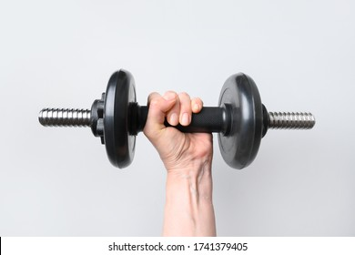 Female hand with black dumbbell on grey background. Sport fitness equipment. Close up.