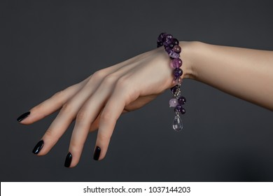 Female hand with black lacquer on nails and a beautiful bracelet of lilac gemstones