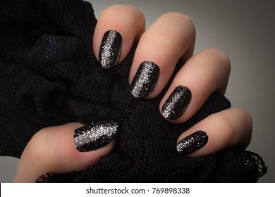 Female hand with black nails and silver glitters is holding black textile on gray background.