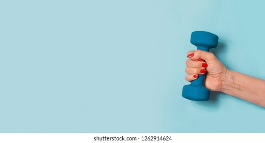 Female hand with blue dumbbell on blue pastel background. Sport concept. Healthy lifestyle.