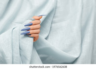 Female hand with blue stiletto nail design. Long nail polish manicure. Woman hand on gray fabric background.