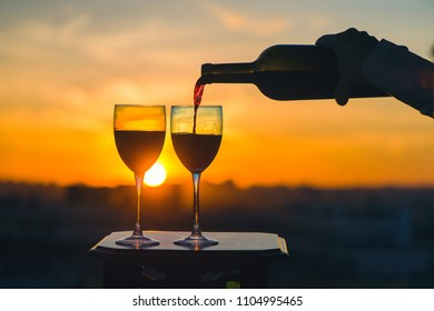 Female hand with bottle pours red wine into glasses on a sunset background. Service on the roof of the restaurant