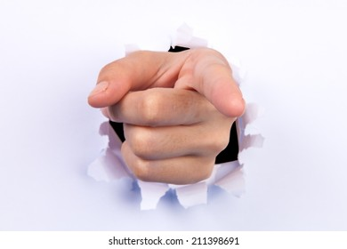 A female hand breaking through paper pointing at you