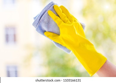 A female hand in bright yellow rubber gloves washes. cleaning the window with a soft rag. Nice view from the window