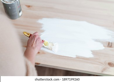 Female hand with a brush to apply white paint on wooden furniture. The concept of renovation, the furniture update.