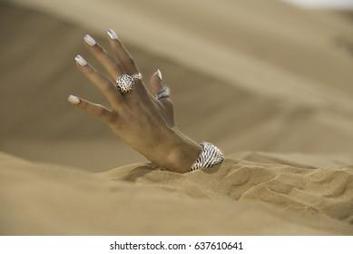 Female hand buried in the desert sand.