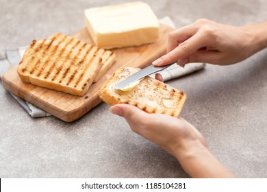 Female hand butters toasts for breakfast on the grey slate background. Horizontal view
