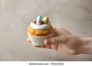 Female hand carrying delicious Easter cupcake on grey background