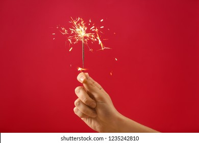 Female hand with Christmas sparkler on color background