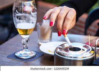Female hand with a cigarette. Ashtray, cigarette and a glass of beer. Female hand with red nails. Bad habits. Danger of disease. Smoking Disease. Harm of smoking.