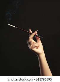 Female hand with cigarette holder on dark background