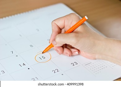 A female hand circling the date of the 15th day in the calendar
