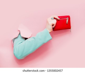 Female hand in classic blue jacket show purse looks out from pink background
