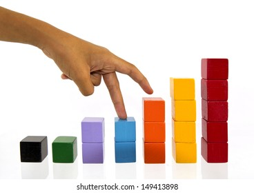 Female hand climbing upstairs which is made from wooden toy blocks