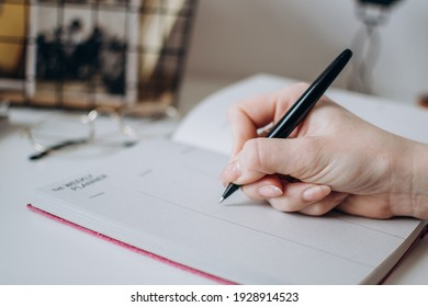 female hand close-up writes with a pen in a notebook. Concept for business woman, writer, personal blog.