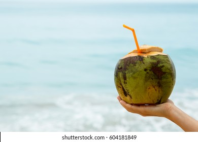 Female hand with a coconut  on the beach