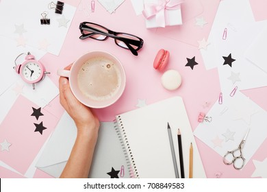 Female hand with coffee cup, macaron, office supply, gift and notebook on pastel desk top view. Fashion pink woman workplace background for blogging. Flat lay. Beautiful morning breakfast.
