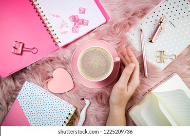 Female hand, coffee cup, notebooks and office supplies on pink woolen fur. Femininity trendy composition. Breakfast, domestic life, weekend, hygge and cozy atmosphere concept