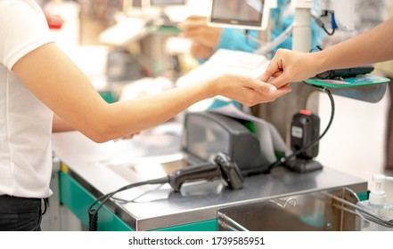 Female hand with coin money pay for goods concept. Hand giving cash and hand receiving cash, paying checkout at cashier access in supermarket.