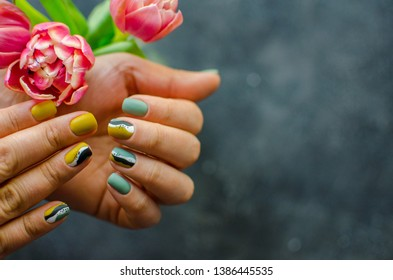 Female hand with colorful matt nails holding pink tulips. dark background. Flat lay photo. Spring nails concept