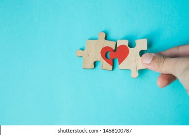 Female hand connecting puzzle with drawn red heart on blue background. Love concept. St. Valentine day. Reconciliation. Reunion concept. Copy space.