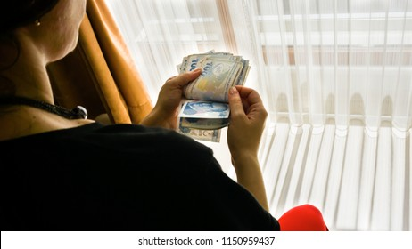 """Female hand counting hundred Turkish Lira. Financial difficulty concept. Bad straits. Cost of living. Turkish government paper banknotes. Closeup of Turkish national currency known as """"Turk Lirasi"""""""