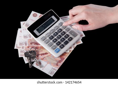 Female hand counts on a calculator. The calculator, five thousandth Russian rubles and keys lie on a black background.  biznes. finansy.  - Shutterstock ID 142174654