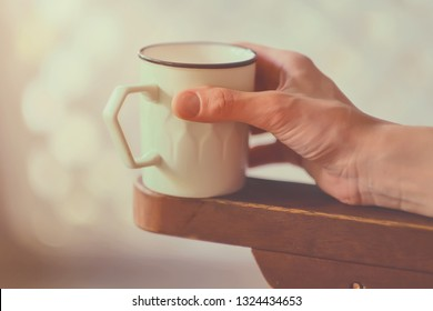 Female hand with cup of coffee or tea in morning light. Coffee cup at home. Girl hand holding a white cup with hot drink.
