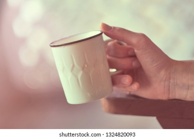Female hand with cup of water in morning light. Water cup at home. Girl hand holding a cup with water.
