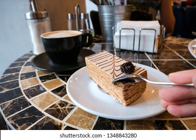 Female hand cutting off piece of delicious sweet cake with spoon to eat it with cappuccino coffee in black cup in restaurant