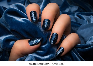 The female hand with dark blue glittered nails is holding blue soft textile as blue textured background.