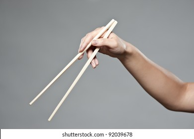 A female hand demonstrating correct oriental chopstick use in open position
