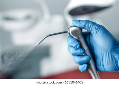 Female hand of dentist in blue gloves holding air water syringe, blurred background of clinic with dental unit, dentistry and teeth care concept with copy space
