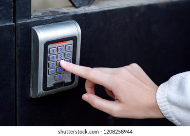 female hand dials the access code on the electronic lock by pressing a finger with a blue backlight, close-up of the security lock with the hand.