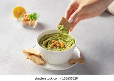 Female hand dipping cracker into white bowl with avocado hummus. healthy vegan dip. close-up. gray background with place for text.