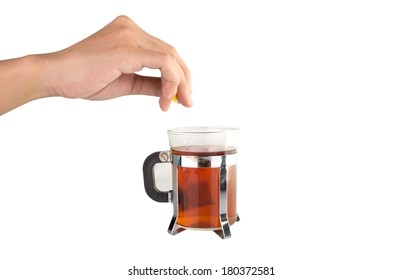 Female hand dipping teabag into a mug of hot water.