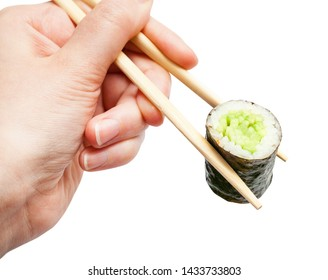 female hand with disposable chopsticks holds kappa maki sushi roll with cucumber close up isolated on white background