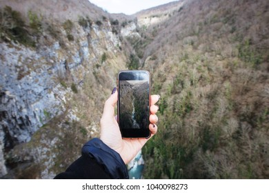Female hand doing mobile photo in mountains valley by sell phone