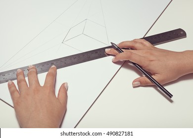 female hand drawing a cube with pen and ruler in two point perspective