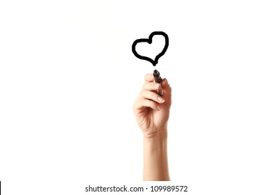 Female hand drawing heart with black marker