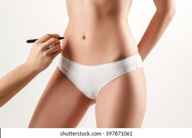 The female hand drawing lines on woman's abdomen