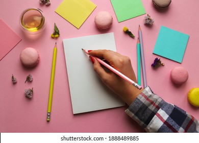 Female hand drawing in sketchbook. Creative feminine workspace with sketchbook for drawing, pencils, a cup of tea and macaroons on pink background. Art concept. Top view, flat lay.