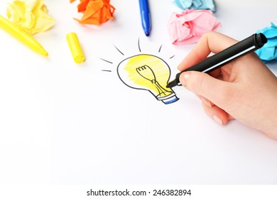 Female hand drawing symbol of idea as light bulb on sheet of paper, on white background