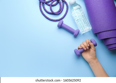 Female hand with dumbbells, bottle of water and yoga mat on color background