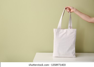 Female hand with eco bag on table against color background
