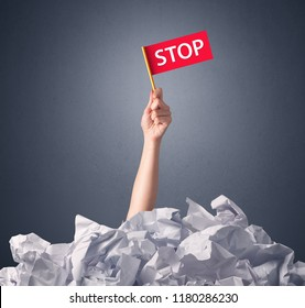 Female hand emerging from crumpled paper pile holding a red flag with stop written on it
