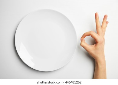 Female hand and empty plate isolated on white
