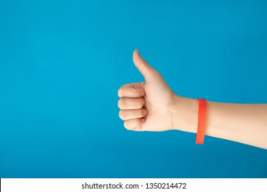 Female hand with empty red bracelet on blue background. Music festival branding empty wristband design. Clear sweat band mock up design.