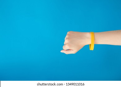 Female hand with empty yellow bracelet on blue background. Music festival branding empty wristband design. Clear sweat band mock up design.