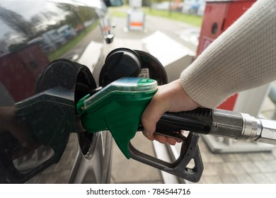 Female hand fill gasoline in a car with gas pump nozzle